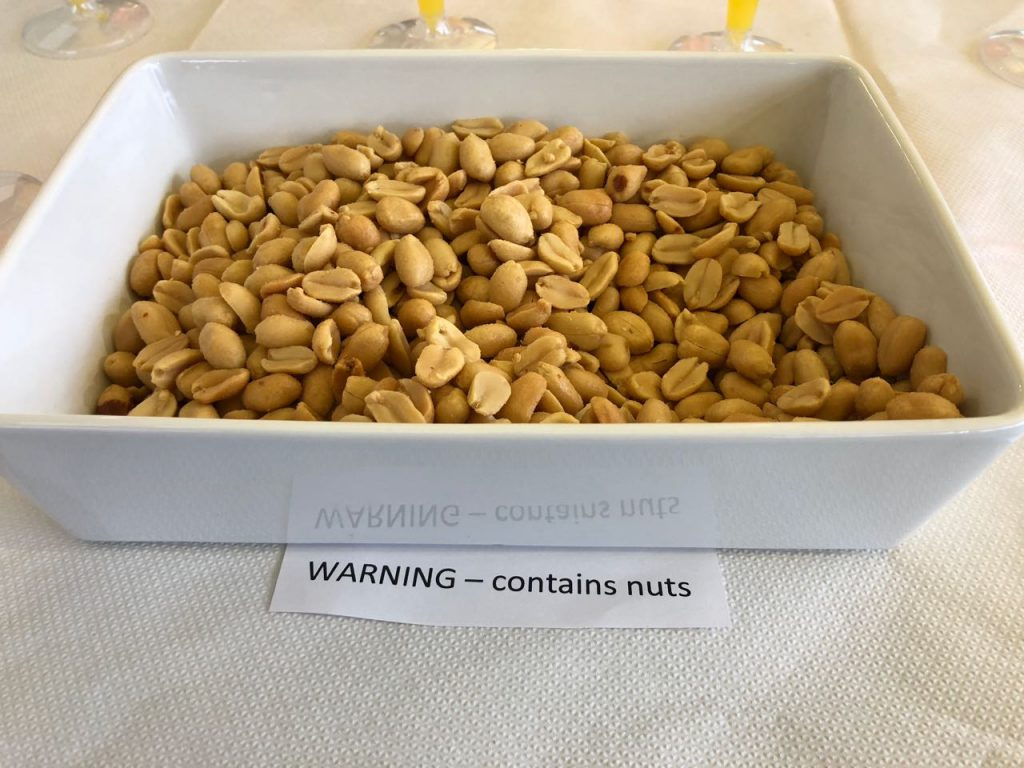 A bowl of nuts with a sign that reads, 'Warning - contains nuts'.